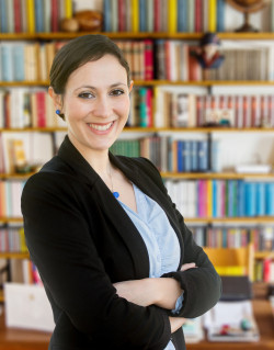 smiling female administrator in front of bookcases